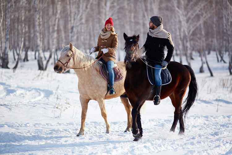 couple riding horse in winter
