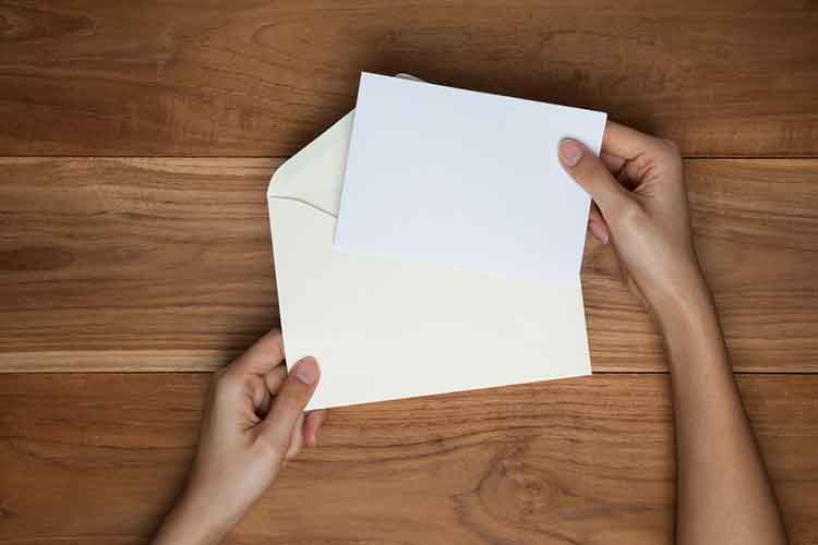 a hand opening an envelope