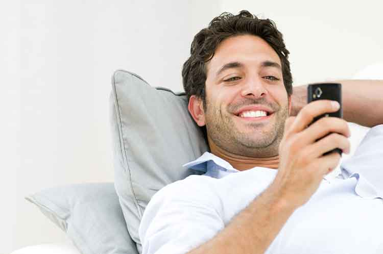 guy looking at cellphone and smiling