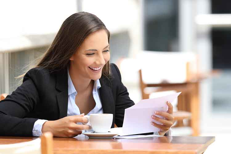 lady smiling after she opens an envelope