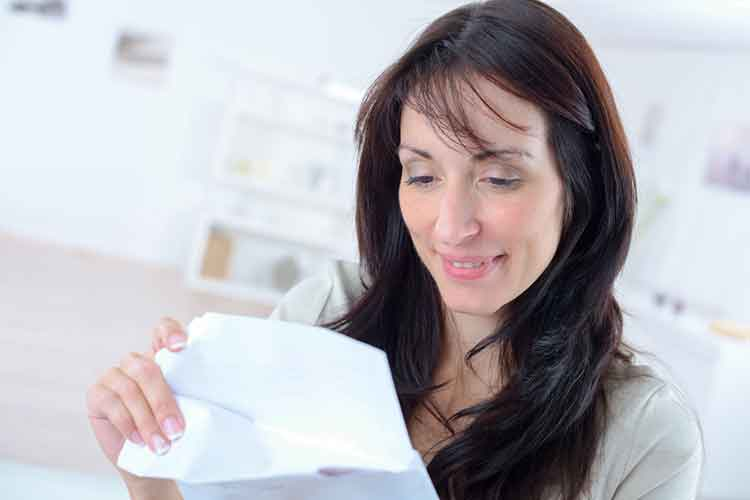 lady smiling as she opens envelope